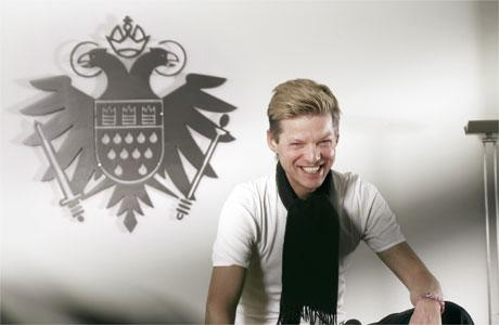 """Wolfgang Voigt ist für alles gewappnet. Hier posiert er als Cheshire Cat vor dem Wappen der """"Speicher""""-Reihe aus dem Kölner Hause Kompakt."""